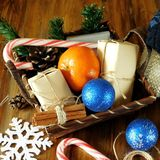 Basket full of Christmas attributes and present boxes on a wooden background Royalty Free Stock Photos