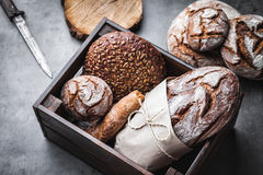 A basket full of delicious fresh bread on wooden background Royalty Free Stock Photos