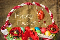 Basket with eggs and embroidered text 'Happy Easter'. Basket full of eggs and embroidered text 'Happy Easter stock image