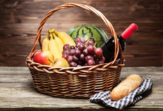 Basket full of fresh fruit. Wooden background Stock Photos