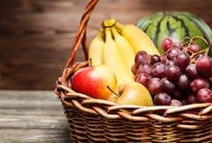 Basket full of fresh fruit. Wooden background Stock Photo