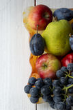 Basket full of fruits. Pear, apple, grape Royalty Free Stock Photos