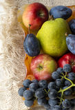 Basket full of fruits. Pear, apple, grape Royalty Free Stock Image