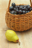 Basket full of grapes with pear Royalty Free Stock Image