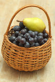 Basket full of grapes with pear on top Royalty Free Stock Image