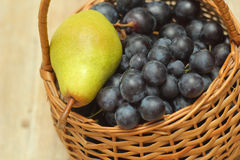 Basket full of grapes with pear on top Stock Photos