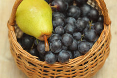 Basket full of grapes with pear on top Stock Images