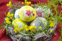 Basket full of handcolored Easter Eggs in decoupage. Against a red background Stock Image