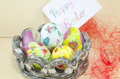 Basket full of handcolored Easter Eggs in decoupage. With a happy easter card in the background Stock Image