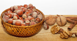 Basket full of hazelnuts on wooden table with walnuts and cinnamon Royalty Free Stock Images