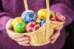 Basket full of multicolored easter eggs in hands pensioner woman royalty free stock photo