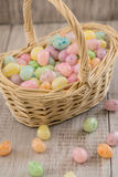 Basket full of pastel colored Easter egg candy. Wicker basket full of pastel colored Easter egg cancy on wood background Stock Photo