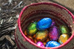 Basket full of shiny foil wrapped chocolate Easter eggs royalty free stock images