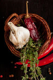 Basket with garlic, chili pepper and thyme Stock Photos