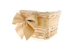 Basket for a gift. Empty wattled basket for a gift for any holiday, decorated with a gold bow Royalty Free Stock Photography