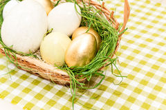 Basket with golden easter eggs Stock Photography