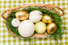 Basket with golden easter eggs Royalty Free Stock Images