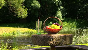 Basket with grape and peach fruit and glass with champagne cider. Basket with grape and peach fruits and glass with champagne cider on millstone table near river stock video footage