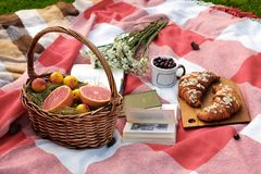 Basket with grapefruit and apricots, a glass with a cherry, a bouquet of white flowers, two croissants on a wooden board, books. stock photos