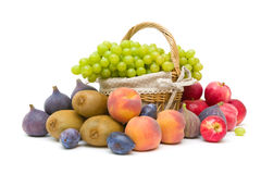 Basket with grapes and other fruit on a white background Royalty Free Stock Photo