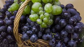 Basket of grapes and vine with green leaves Royalty Free Stock Photography