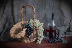 Basket of grapes and wine. Basket with grapes, and a bottle of wine ready to be poured into the wine glasses setting on the table Royalty Free Stock Images