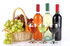 Basket with grapes and wine bottles. Bottles of wine with basket full of grapes on white background Stock Photography