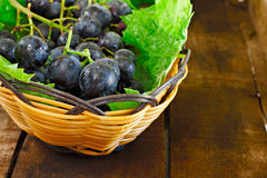 Basket of grapes on wooden table Royalty Free Stock Images