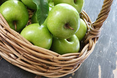 Basket of Green Apples. Cane basket of green Granny Smith apples, on rustic tabletop royalty free stock images