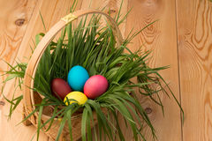 Basket with green grass and Easter eggs on wooden Stock Photo