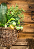 Basket with green vegetables on an old wooden  table Royalty Free Stock Image