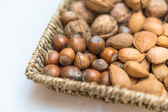 Basket with hazelnuts and almonds. A basket with walnuts, Almonds, Brazil nuts, hazel nuts and a nut cracker royalty free stock image