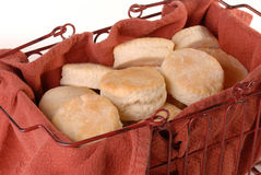Basket of homemade baked biscuits. Homemade biscuits baked ready to eat in a rustic basket with a red towel inside to keep biscuits warm Stock Photos