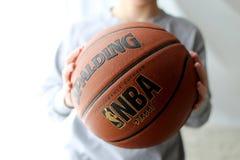 Basket i en unges händer Arkivbild