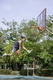 Basket i kast för handmanbanhoppning som ett träd för bakgrund för basketbeslag parkerar in arkivfoton
