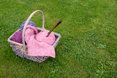 Basket of knitting, needles and wool on a lawn Stock Images
