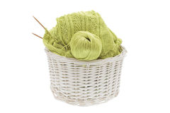 Basket of knitting and yarn. Wicker basket of knitted cotton fabric, bamboo needles and yarn on a white background Royalty Free Stock Photo