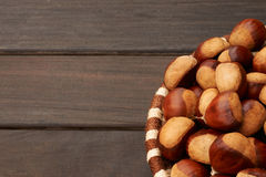 Basket of large chestnuts. On a dark wood table Royalty Free Stock Photos