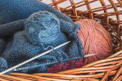 in a basket lay coils of thread for knitting with knitting needles_ stock photo