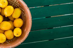 Clay pot basket of lemons on the coloful table with copyspace. Clay pot basket of lemons on the coloful table view from above with copyspace stock photography
