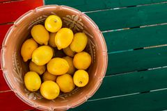 Clay pot basket of lemons on the coloful table with copyspace. Clay pot basket of lemons on the coloful table view from above with copyspace royalty free stock photo