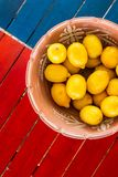 Clay pot basket of lemons on the coloful table with copyspace. Clay pot basket of lemons on the coloful table view from above with copyspace royalty free stock photography