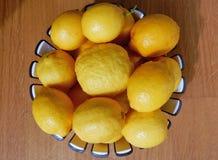 Basket of lemons on parquet. Basket of organic Sicilian lemons on oak parquet Royalty Free Stock Image
