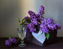 Basket with lilac and a glass of water. Royalty Free Stock Image