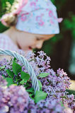 Basket of lilacs in spring garden and child girl Stock Photography