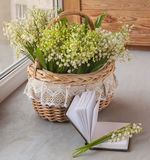 Basket with lilies of the valley (Convallaria majalis) and noteb Royalty Free Stock Photos