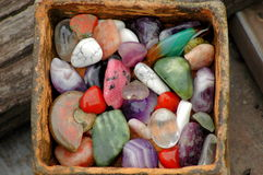 Basket with a lot of natural stones. Many colourful minerals in a ceramical vase hand made Royalty Free Stock Photography