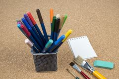 Basket with makers pens. In a cork background royalty free stock image