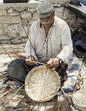 Basket Making. Editorial. Ermoupolis: June 28. Male Greek Gypsy weaving handmade baskets by the side of the road. Ermoupolis, Syros June 28 2018. Greece Royalty Free Stock Images
