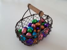 Basket of metal thread with wooden handle and coloured easter eggs in it. Metal threaded basket with wooden handle, filled with chocolate easter eggs in purple stock photo